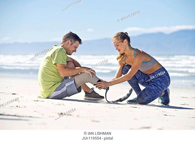 Woman Helping Man To Attach Prosthetic Blade Before Exercising On Beach Together