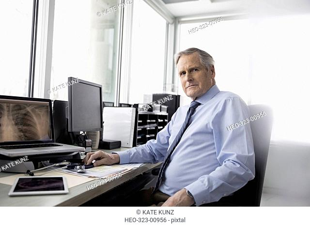 Portrait serious, confident male doctor reviewing x-rays on computer in clinic doctor