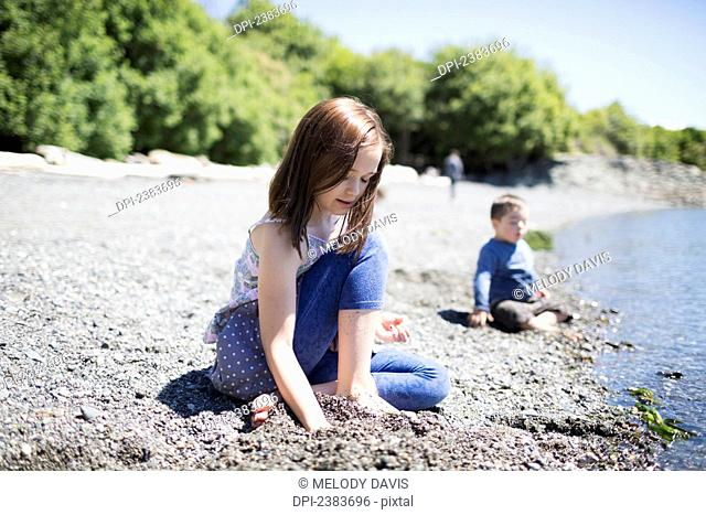 A brother and sister sit in the sand at the water's edge; Victoria, British Columbia, Canada
