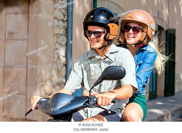 Young couple riding moped together through village, Majorca, Spain