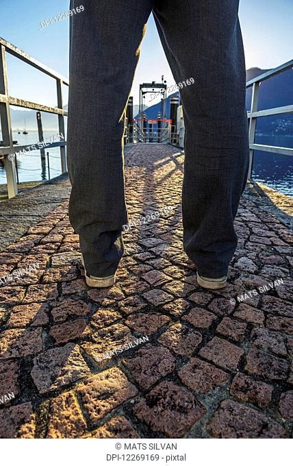 Man standing on a stone walkway on the waterfront; Locarno, Ticino, Switzerland