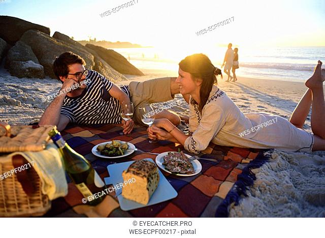Happy couple having a picnic on the beach at sunset