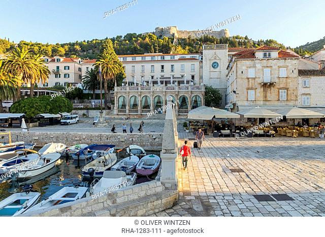 The main square (Trg Svetog Stjepana) of Hvar Town with view to the Spanish Fortress in the background at first sunlight, Hvar, Croatia, Europe