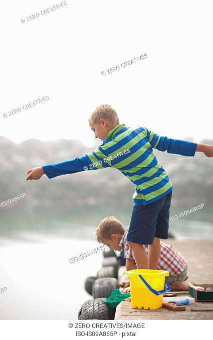 Two young boys fishing on pier