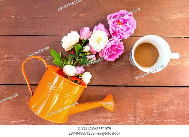 Bouquet of pink roses in a vase and a cup of coffee on a table. Home interior with coffee and flowers. Tinted image. Vintage photo. Space for text