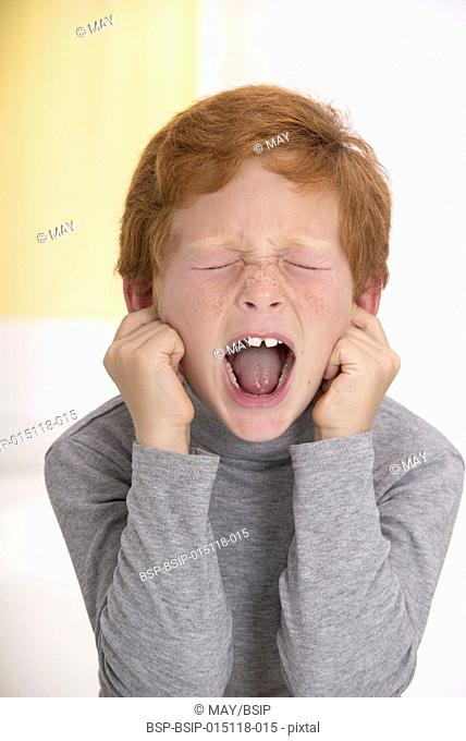 Boy sticking fingers in his ears