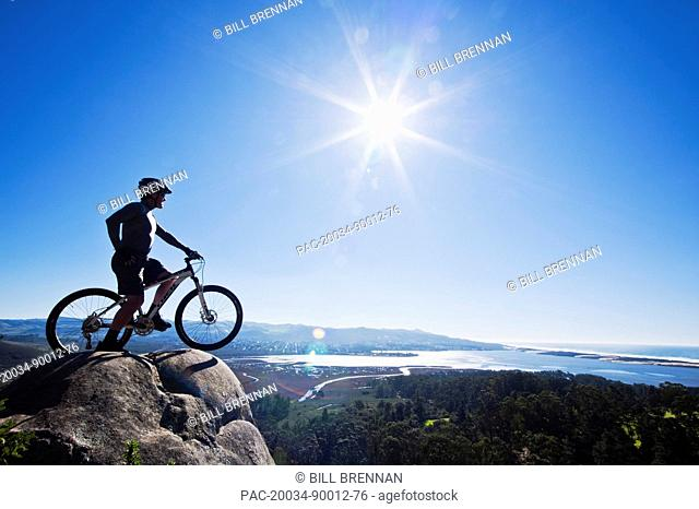 California, Morro Bay State Park, Man on bicycle looks over Morro Bay from cliff