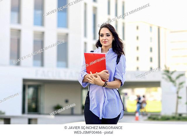 Portrait of student with notebooks on campus