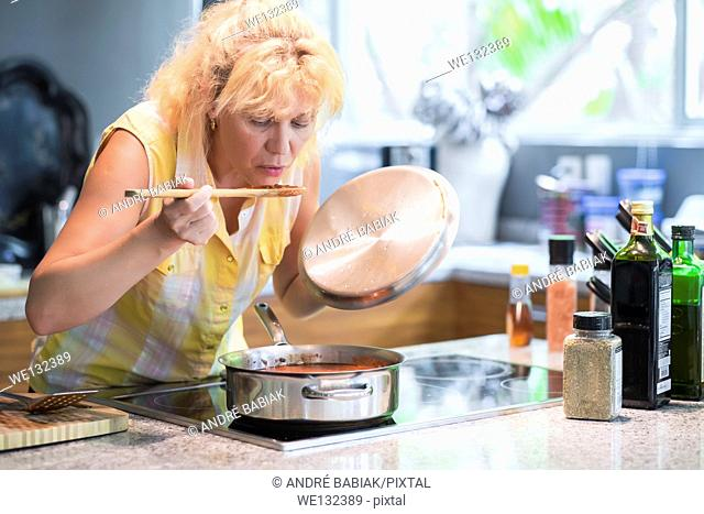 A woman is taking a taste of a red tomato sauce on a wooden spoon in her kitchen