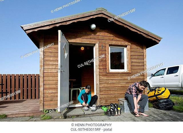 Family putting on shoes outside shed