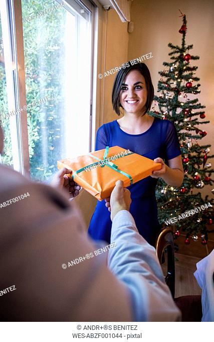 Woman handing over Christmas present to man