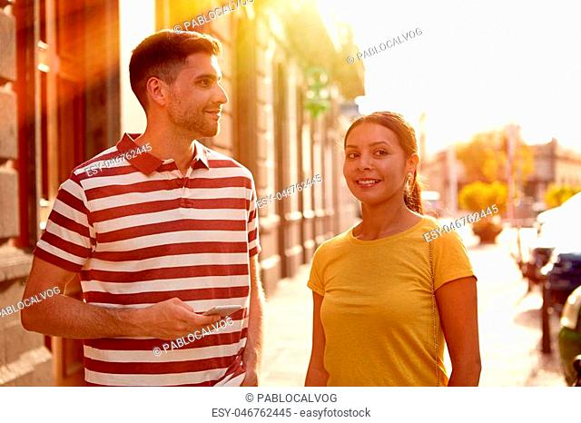 Young couple looking away talking and smiling happily while dressed casually in t-shirts with old buildings behind them
