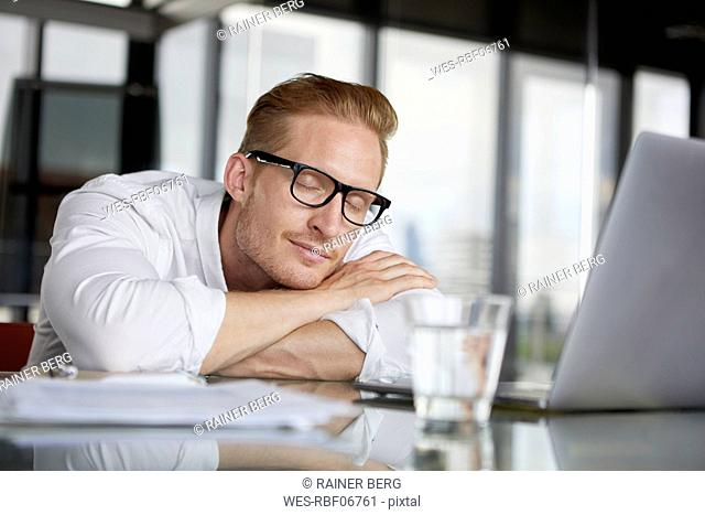 Businessman leaning on desk in office with closed eyes