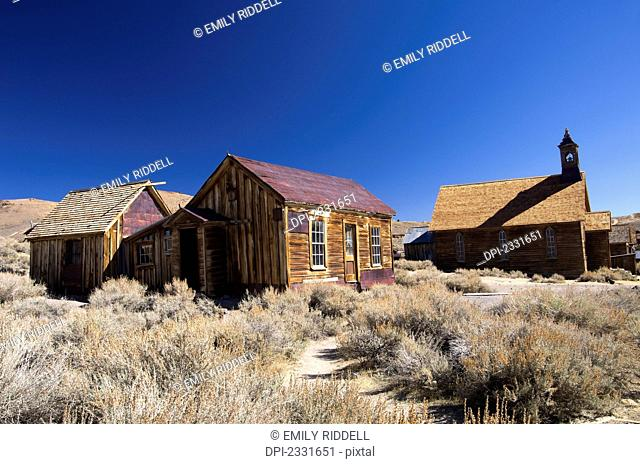 Gold mining ghost town with weathered buildings in the sage brush;Bodie california united states of america