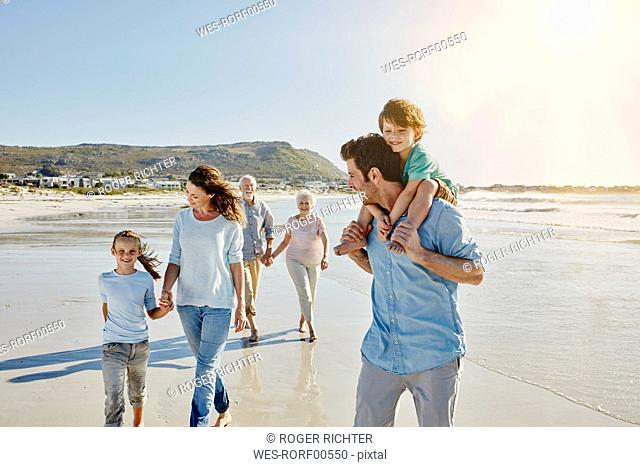 Three generations family strolling on the beach