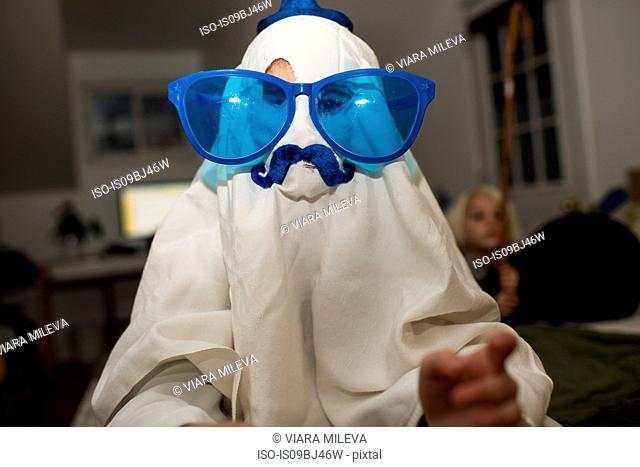 Girl dressed up as ghost with mustache and over sized sunglasses