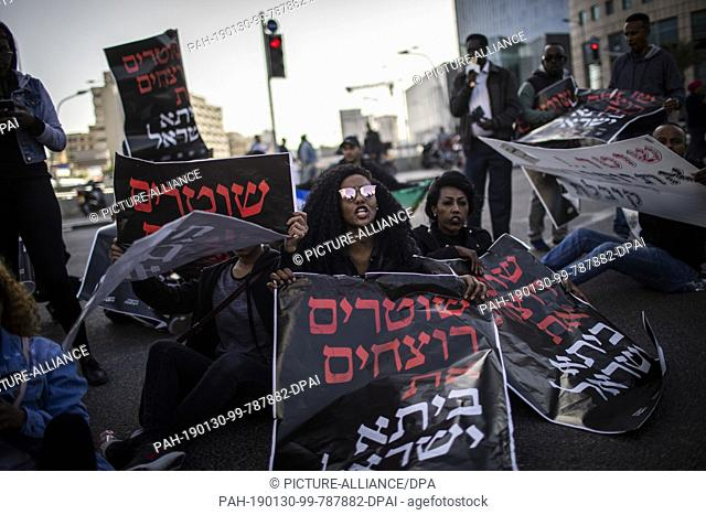 30 January 2019, Israel, Tel Aviv: An Ethiopian-Israeli woman holds a placard while shouting slogans during a protest against alleged police brutality