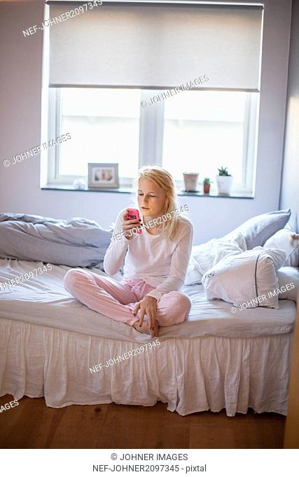 Teenage girl with cell phone on bed