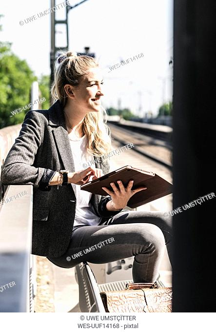 Young woman sitting at train station, using digital tablet