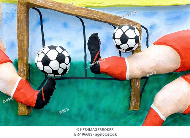 Two footballers are shooting simultaneously two balls, caricature made of paper maché , monday before lent parade, Duesseldorf, NRW, Germany
