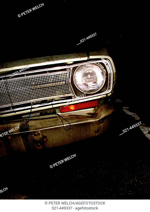 Single headlight of an old Plymouh automobile from the 1960's