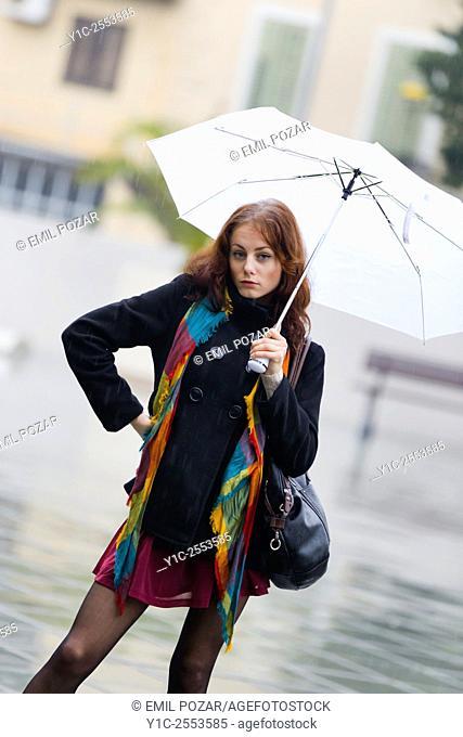 Teenager girl under White umbrella on rainy day