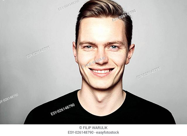 Studio shot of young man smiling to camera. Isolated on white background. Horizontal format, he is looking to the camera, he is wearing a black T-shirt