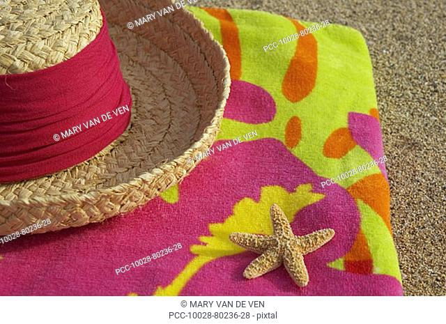 Straw hat and seastar on multi-colored towel, on sandy beach
