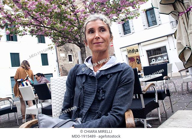 Woman sitting in an outdoor caf̩. Treviso (Italy) 4th april 2014