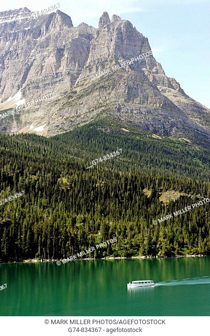 Pretty Lake of Glacier National Park in Montana, USA, with a tourboat