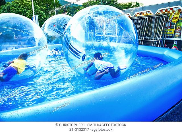 Children zorbing in a large blue paddling pool having fun
