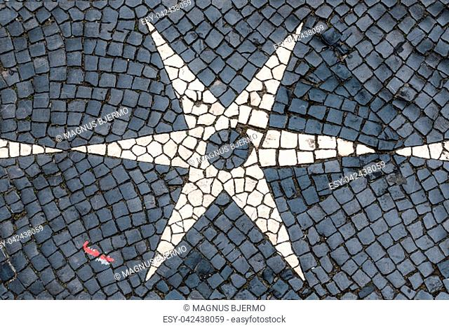 Classic black and white shiny cobblestones set in symmetric star design shapes in street in central Lisbon Portugal