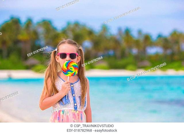 Adorable little girl have fun with lollipop on the beach
