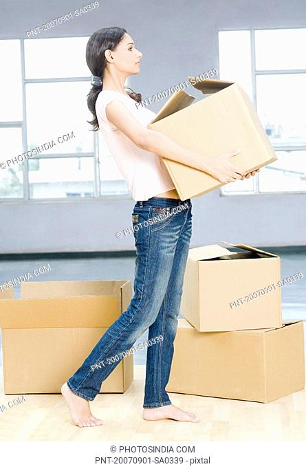 Side profile of a young woman carrying a cardboard box