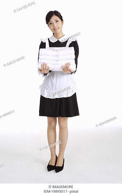 Young waitress holding a stack of towels
