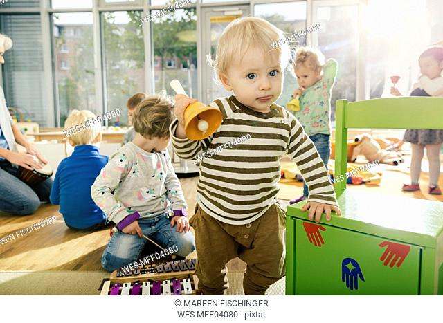 Toddler ringing a bell in music room of a kindergarten