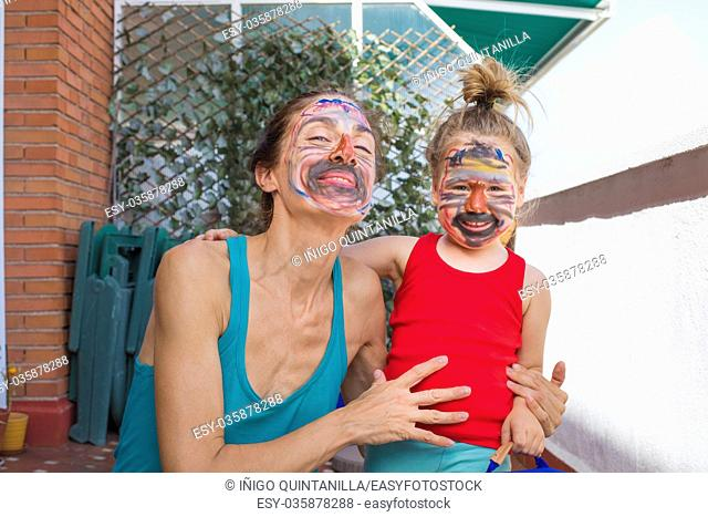 portrait of happy family, woman and three years old child painted faces, looking smiling, in terrace of house
