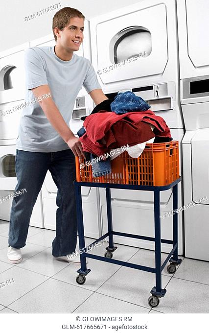Man pushing a laundry basket in a laundromat