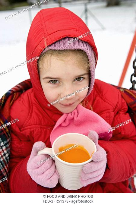 Girl drinking hot soup on swings in snow - With Model Release