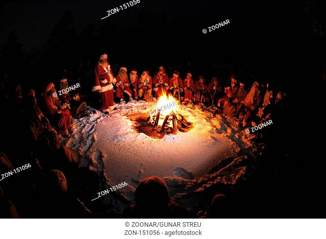 Weihnachtsmaenner sit in a circle around a campfire