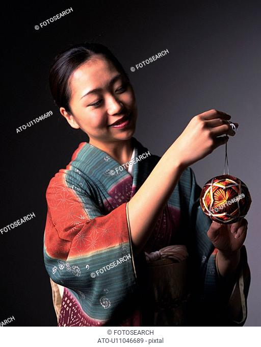 A woman in kimono holding a temari ball, Front View