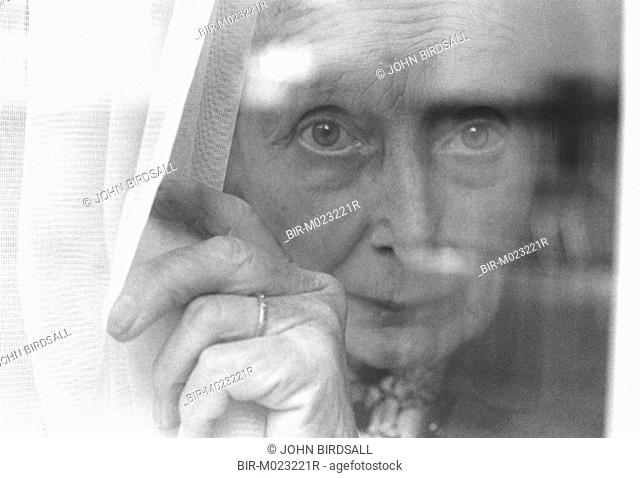 Elderly woman standing at window looking through curtains