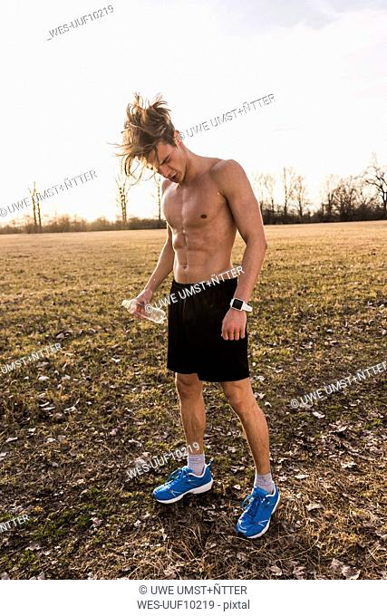 Barechested athlete having a break in rural landscape