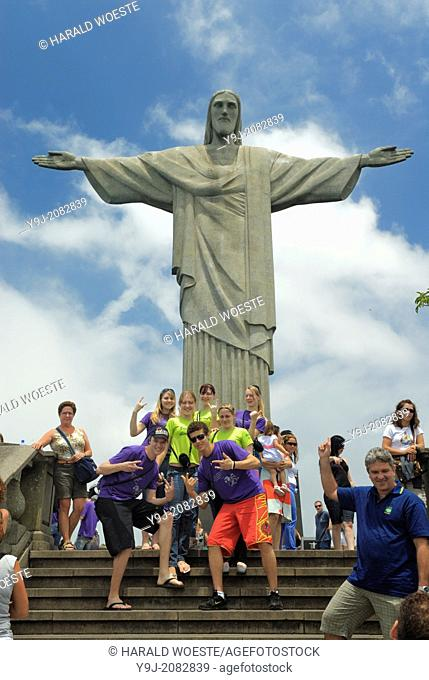 Brazil, Rio de Janeiro: Group of tourists posing for a photograph in front of the iconic Cristo Redentor statue on Corcovado