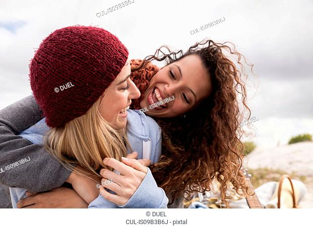 Two young female friends hugging at beach, Western Cape, South Africa