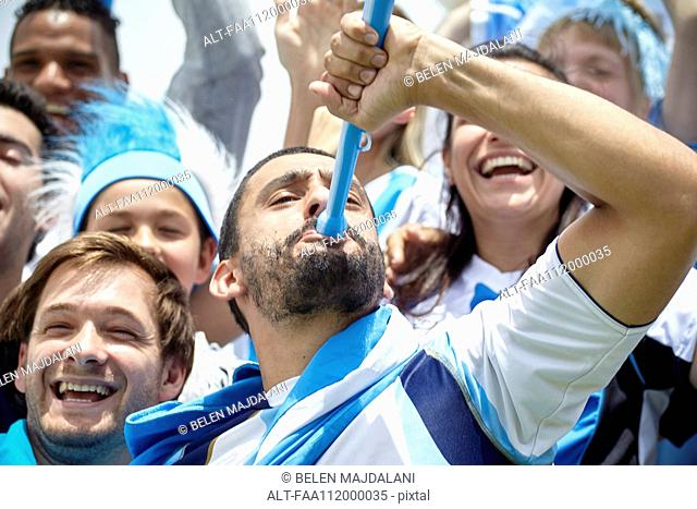 Argentinian football fan playing vuvuzela at match