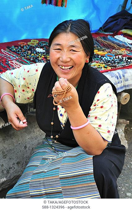 Tibetan woman selling traditional Tibetan accessories on the street shop