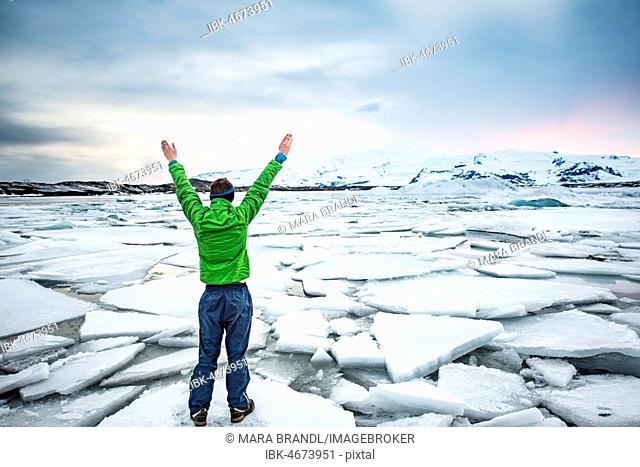Hiker holding his hands up, standing on an ice floe, Jökulsárlón Glacier Lagoon, glacial lake, sunset, southern edge of Vatnajökull, Southeast Iceland, Iceland