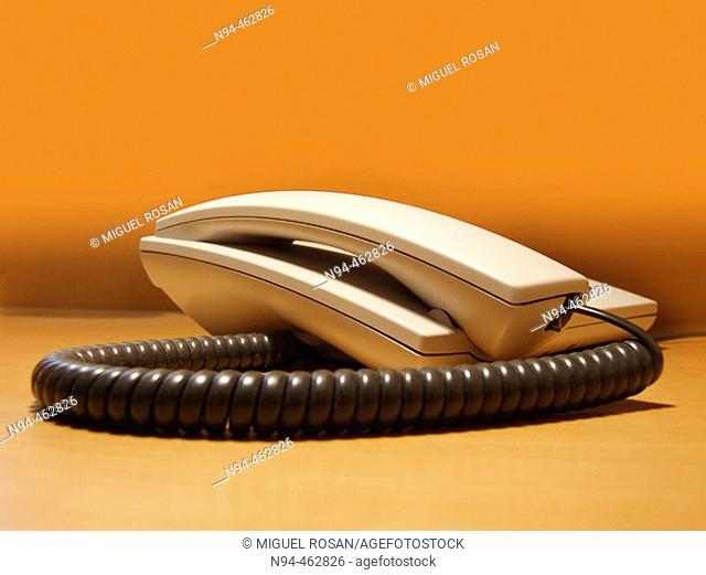 Old and classic desk phone with orange background