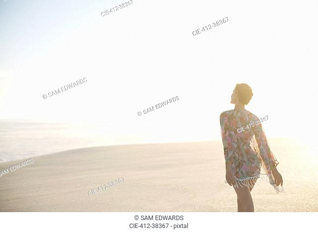 Serene woman in swimsuit coverup walking on sunny summer beach